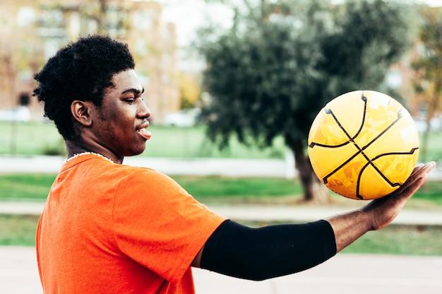 Zwarte afro-amerikaanse jongen basketbal spelen met een gele bal op een stedelijke rechtbank.