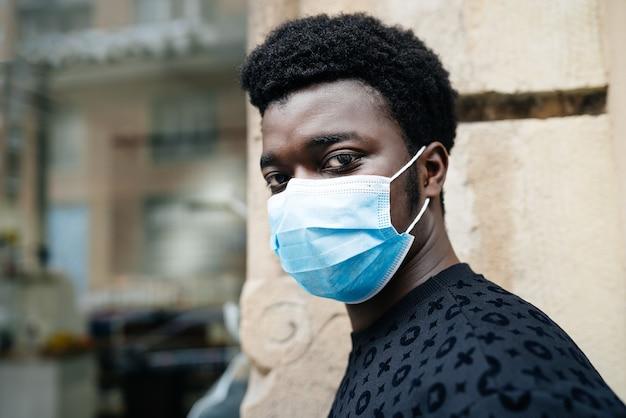 Zwarte afro-amerikaanse jongen die door de straat loopt met een blauw gezichtsmasker en zichzelf beschermt tegen de coronavirus-pandemie covid-19