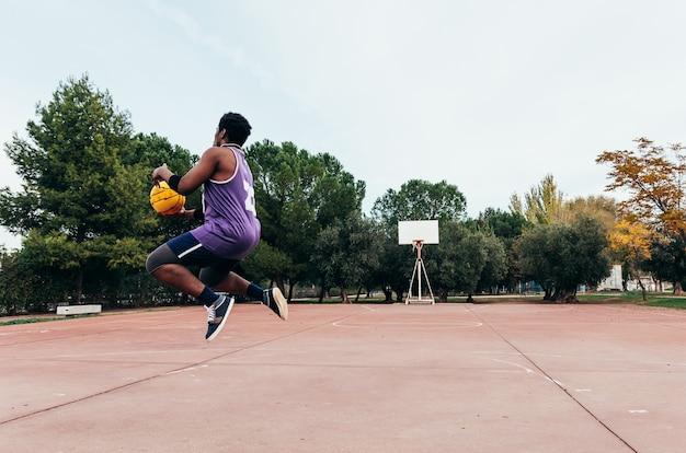 Zwarte afro-amerikaanse jongen die op en neer springt om de mand te schieten. gekleed in een paars mouwloos t-shirt