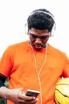 Zwarte afro-amerikaanse jongen, luisteren naar muziek met een koptelefoon en zijn mobiele telefoon na het spelen van basketbal op een stedelijke rechtbank. gekleed met een oranje t-shirt.