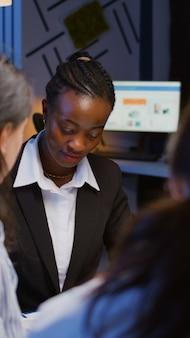 Zwarte afro-amerikaanse manager brainstormt bedrijfsideeën die managementpresentatiepapieren controleren...