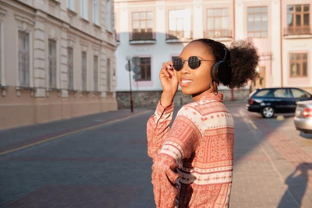 Zwarte afro-amerikaanse meisje heeft een wandeling in de avond stad en luisteren naar muziek in de koptelefoon. meisje in zonnebril in de zomerglimlachen en het kijken op zonsondergang.
