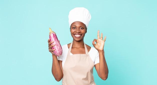 Zwarte afro-amerikaanse volwassen chef-kok vrouw met een aubergine