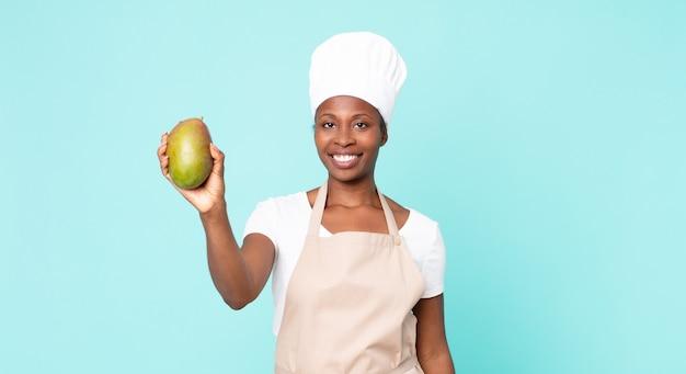 Zwarte afro-amerikaanse volwassen chef-kok vrouw met een mango