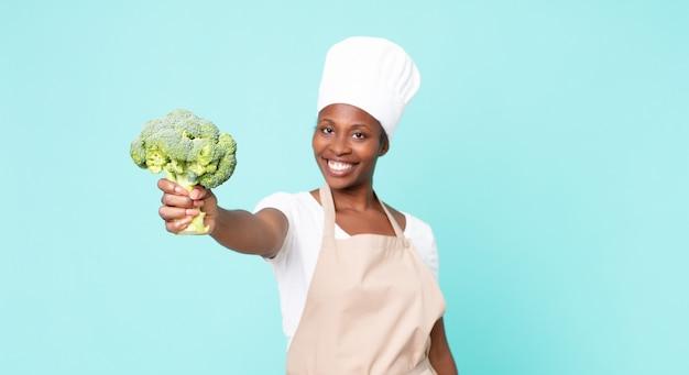 Zwarte afro-amerikaanse volwassen chef-kokvrouw die een broccoli houdt