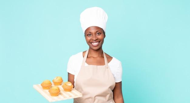 Zwarte afro-amerikaanse volwassen chef-kokvrouw die een muffinsdienblad houdt