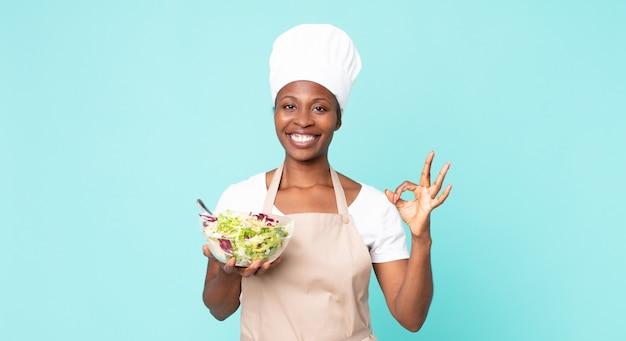 Zwarte afro-amerikaanse volwassen chef-kokvrouw die een salade houdt