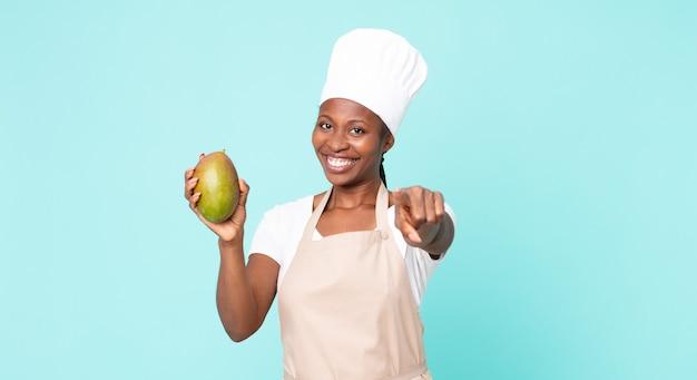 Zwarte afro-amerikaanse volwassen chef-kokvrouw met een mango