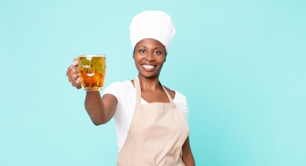 Zwarte afro-amerikaanse volwassen chef-kokvrouw met een pintbier
