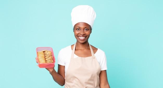 Zwarte afro-amerikaanse volwassen chef-kokvrouw met een tupperware