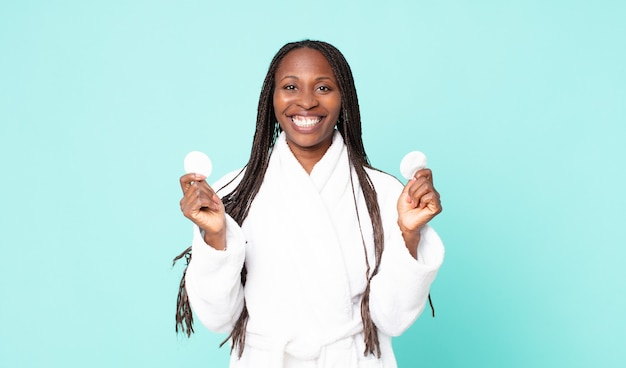 Zwarte afro-amerikaanse volwassen vrouw die een badjas draagt en een gezichtsreinigingskatoen vasthoudt