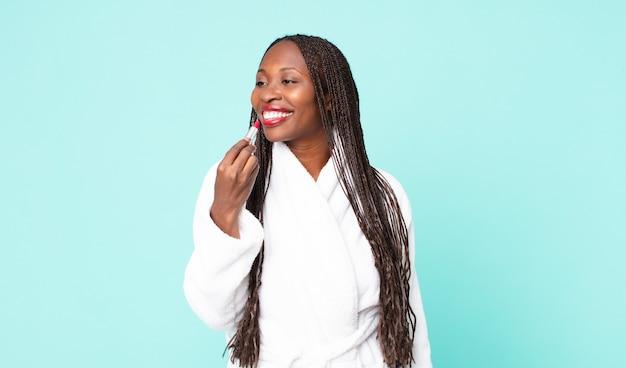 Zwarte afro-amerikaanse volwassen vrouw die een badjas draagt en een lippenstift vasthoudt