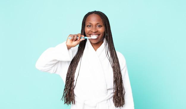 Zwarte afro-amerikaanse volwassen vrouw die een badjas draagt en een tandenborstel vasthoudt