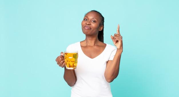 Zwarte afro-amerikaanse volwassen vrouw en met een pint bier