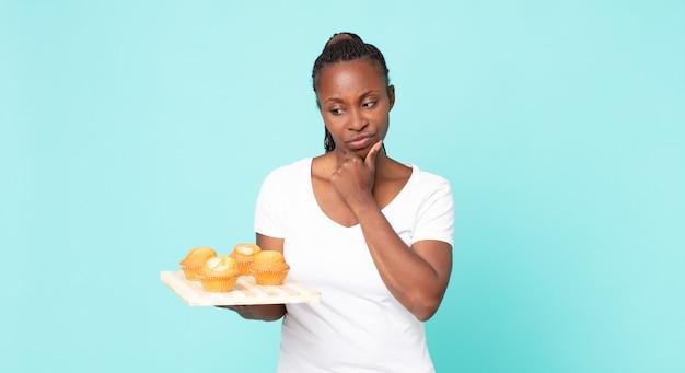Zwarte afro-amerikaanse volwassen vrouw met een dienblad met muffins