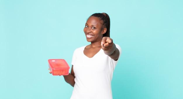 Zwarte afro-amerikaanse volwassen vrouw met een tupperware