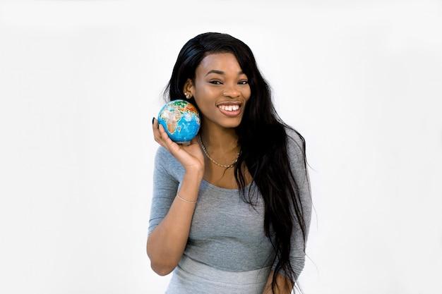 Zwarte afro-amerikaanse vrouw houdt een wereldbol in haar handen