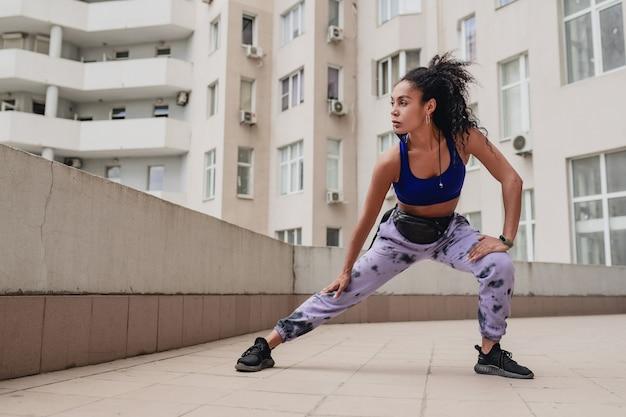 Zwarte afro-amerikaanse vrouw in sport fitness stedelijke outfit op het dak om te trainen