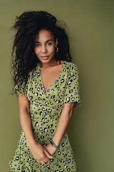 Zwarte afro-amerikaanse vrouw poseren in stijlvolle groene jurk met luipaardprint geïsoleerd op groen