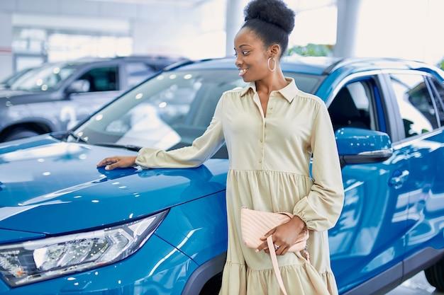 Zwarte afro-amerikaanse vrouw poseren naast blauwe auto in dealer