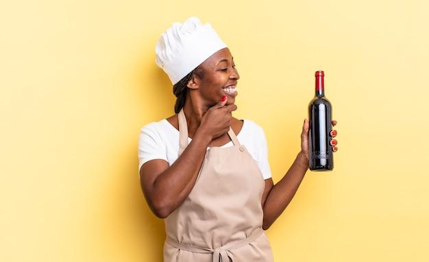 Zwarte afro chef-kok vrouw die lacht met een gelukkige, zelfverzekerde uitdrukking met de hand op de kin, zich afvragend en opzij kijkend. wijnfles concept