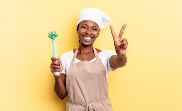 Zwarte afro chef-kok vrouw lacht en ziet er gelukkig, zorgeloos en positief uit, gebarend overwinning of vrede met één hand. afwas concept