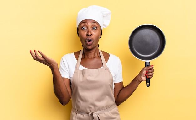 Zwarte afro chef-kok vrouw met open mond en verbaasd, geschokt en verbaasd met een ongelooflijke verrassing