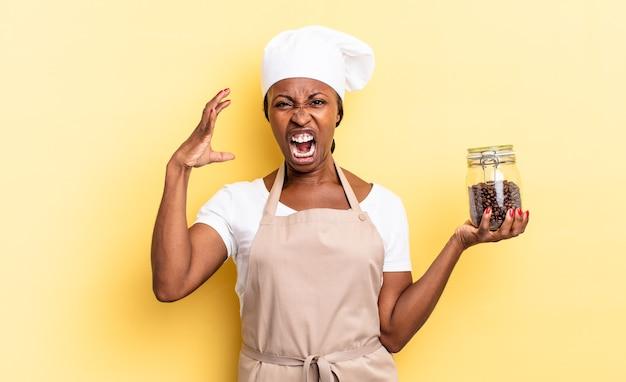 Zwarte afro chef-kok vrouw schreeuwen met handen in de lucht, woedend, gefrustreerd, gestrest en overstuur voelen. koffiebonen concept