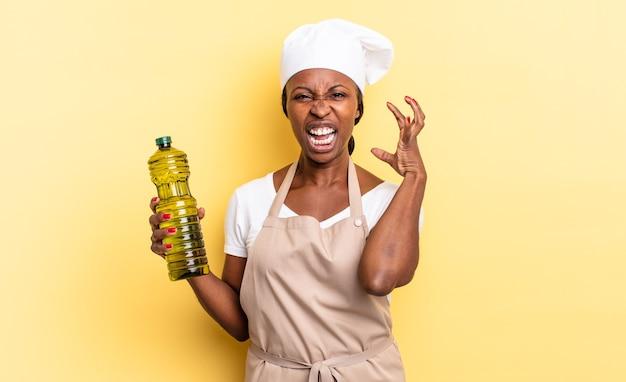 Zwarte afro chef-kok vrouw schreeuwen met handen in de lucht, woedend, gefrustreerd, gestrest en overstuur voelen. olijfolie concept