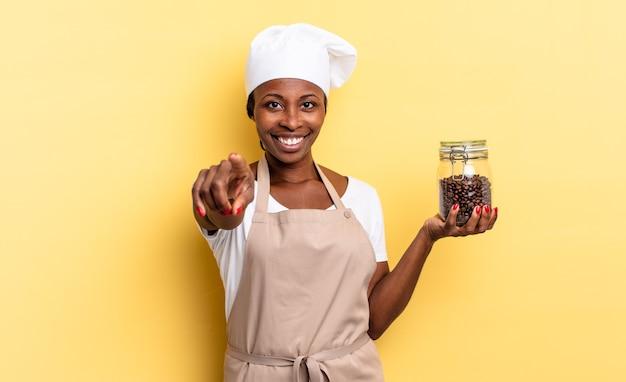 Zwarte afro chef-kok vrouw wijzend op camera met een tevreden, zelfverzekerde, vriendelijke glimlach, jou kiezen. koffiebonen concept