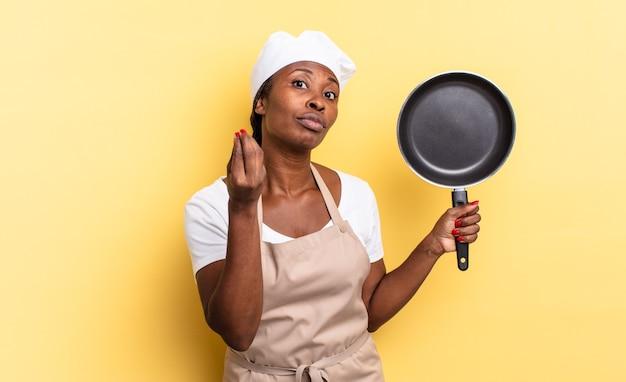 Zwarte afro-chef-kokvrouw die capice of geldgebaar maakt en u vertelt om uw schulden te betalen!