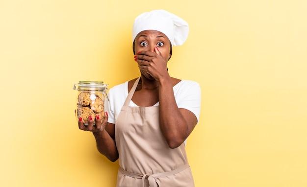 Zwarte afro-chef-kokvrouw die mond bedekt met handen met een geschokte, verbaasde uitdrukking, een geheim houdt of oeps zegt. koekjes concept