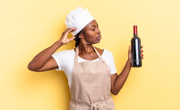 Zwarte afro-chef-kokvrouw die vrolijk lacht en dagdroomt of twijfelt, opzij kijkend. wijnfles concept