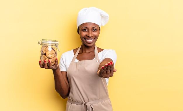 Zwarte afro-chef-kokvrouw die vrolijk lacht met een vriendelijke, zelfverzekerde, positieve blik, een object of concept aanbiedt en toont. koekjes concept