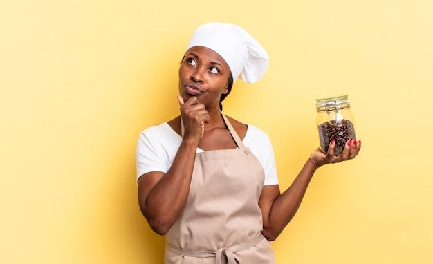 Zwarte afro-chef-vrouw denkt, voelt zich twijfelachtig en verward, met verschillende opties, zich afvragend welke beslissing ze moet nemen. koffiebonen concept