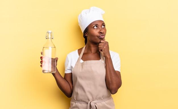 Zwarte afro-chef-vrouw denkt, voelt zich twijfelachtig en verward, met verschillende opties, zich afvragend welke beslissing ze moet nemen om een waterfles vast te houden