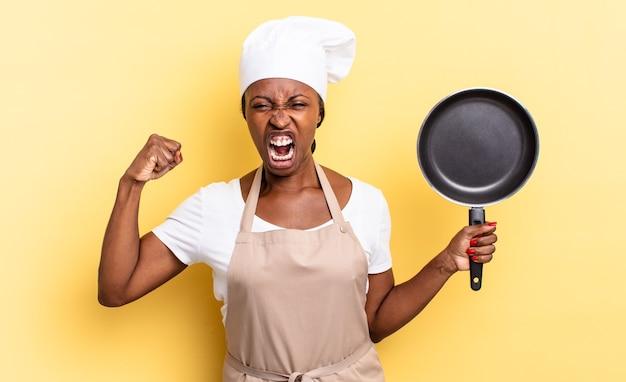 Zwarte afro-chef-vrouw die agressief schreeuwt met een boze uitdrukking of met gebalde vuisten om succes te vieren