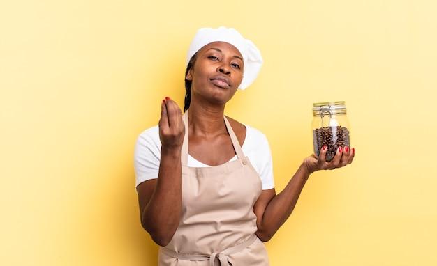 Zwarte afro-chef-vrouw die capice of geldgebaar maakt en u vertelt uw schulden te betalen!. koffiebonen concept Premium Foto