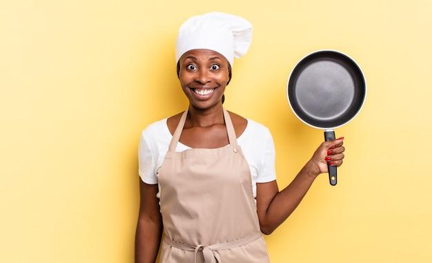Zwarte afro-chef-vrouw die er blij en aangenaam verrast uitziet, opgewonden met een gefascineerde en geschokte uitdrukking