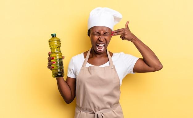 Zwarte afro-chef-vrouw die er ongelukkig en gestrest uitziet, zelfmoordgebaar maakt een pistoolteken met de hand, wijzend naar het hoofd. olijfolie concept