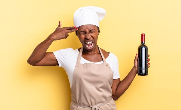 Zwarte afro-chef-vrouw die er ongelukkig en gestrest uitziet, zelfmoordgebaar maakt een pistoolteken met de hand, wijzend naar het hoofd. wijnfles concept