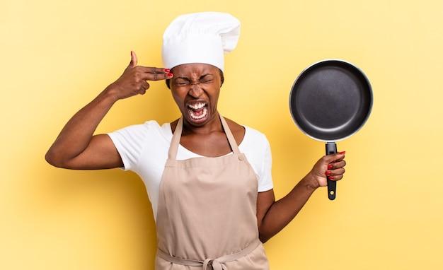 Zwarte afro-chef-vrouw die er ongelukkig en gestrest uitziet, zelfmoordgebaar maakt een pistoolteken met de hand, wijzend naar het hoofd