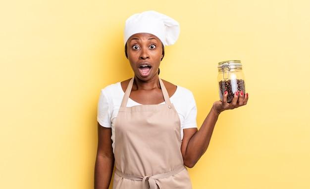 Zwarte afro-chef-vrouw die erg geschokt of verrast kijkt, starend met open mond en zegt wauw. koffiebonen concept