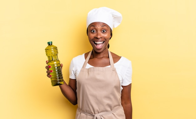 Zwarte afro-chef-vrouw die erg geschokt of verrast kijkt, starend met open mond en zegt wauw. olijfolie concept