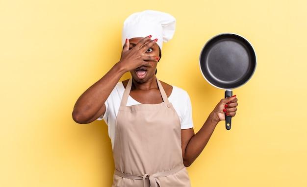 Zwarte afro-chef-vrouw die geschokt, bang of doodsbang kijkt, haar gezicht bedekt met de hand en tussen de vingers gluurt
