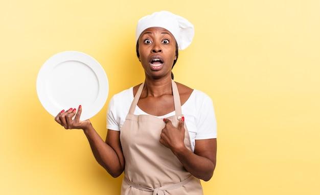 Zwarte afro-chef-vrouw die geschokt en verrast kijkt met wijd open mond, wijzend naar zichzelf. leeg bord concept
