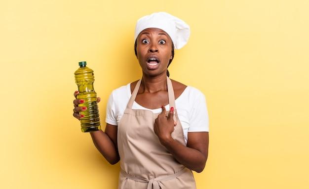 Zwarte afro-chef-vrouw die geschokt en verrast kijkt met wijd open mond, wijzend naar zichzelf. olijfolie concept