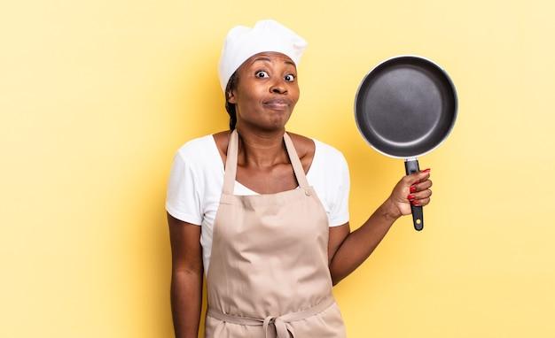 Zwarte afro-chef-vrouw die haar schouders ophaalt, zich verward en onzeker voelt, twijfelt met gekruiste armen en een verbaasde blik