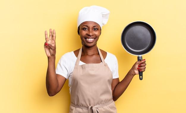 Zwarte afro-chef-vrouw die lacht en er vriendelijk uitziet, nummer drie of derde toont met de hand naar voren, aftellend