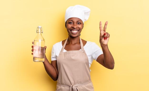 Zwarte afro-chef-vrouw die lacht en er vriendelijk uitziet, nummer twee of seconde toont met de hand naar voren, aftellend met een waterfles